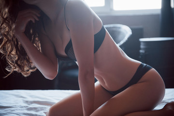 A beautiful thin young woman lays in a bed with long hair in black lingerie.