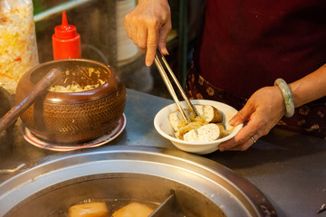 A woman serves stinky tofu at the night market of Jiufen