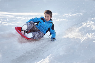 Boy sledding down a hill in the snow