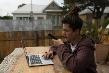 Male skateboarder talking on mobile phone while using laptop