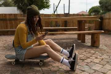 Female skateboarder using mobile phone while sitting on