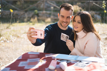 Pregnant woman and her husband makes a selfie with ultrasound image outside. Pregnancy, parenthood, preparation and expectation concept.