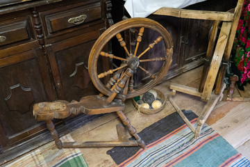 Traditional devices, vintage tailoring equipment concept. Fashioned wooden distaff, spindle, spinning wheel.