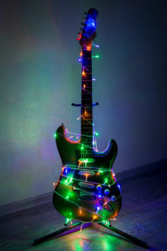 Electric guitar wrapped in colorful garland, the idea of holiday music