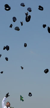 Air Force officers throw their caps in the air, as they celebrate after their graduation ceremony at the Brazilian Air Force Academy (AFA) in Pirassununga