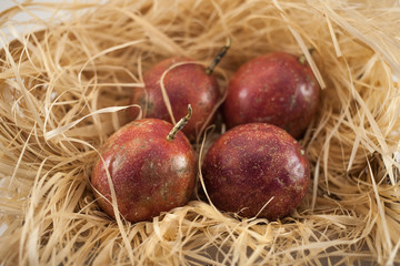 Four passion fruit isolated. Whole maracuyas on straw