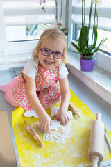 Cute little girl with roller pin preparing Christmas cookies