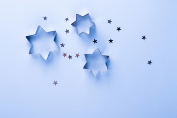 Holiday background. Group of little silver stars on blue pastel background. Top view. Copy space.