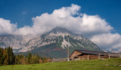 Alpine landscape on a sunny day. Colorful autumn scene. Mountain and a huge cloud above it. In the foreground is a relay tower and an alpine shed. Amazing natural background. South Tyrol Austria