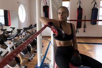 Female boxer relaxing in boxing ring at fitness studio