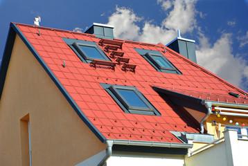 Mit rot beschichteten Metall-Ziegeln gedecktes Dach mit modernen Dachfenstern, Dachtreppe, Schneefang und mit beschichtetem Metall verkleideten Schornsteinen Stehfalz-Metalldach mit Gaubenfenstern