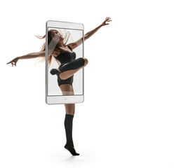 Photo of young beautiful graceful ballerina dancing on white background, concept virtual reality of the smartphone. going out of the device
