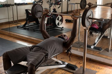 Male boxer exercising with bench press barbell in fitness studio