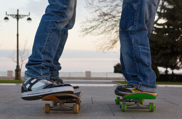 Two young guys stand on skateboards