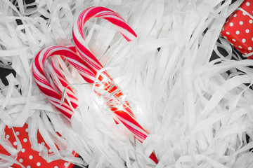 Christmas candy canes and red gift boxes illuminated by garland and placed on white paper sawdust