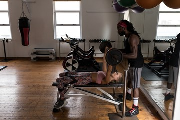 Trainer assisting female boxer in lifting barbell at fitness