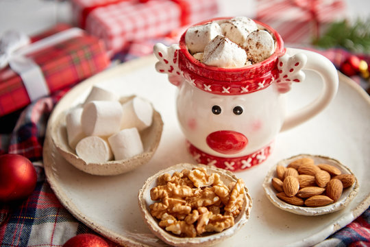 Delicious homemade christmas hot chocolate or cocoa with marshmellows in a red xmas decorative cup. With almonds, walnuts in small bowls on side