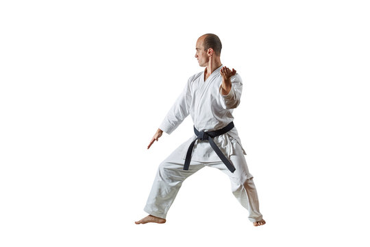 Black belt athlete performs formal karate exercises on a white isolated background