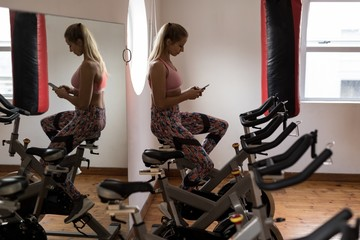 Female boxer using mobile phone while exercising on exercise