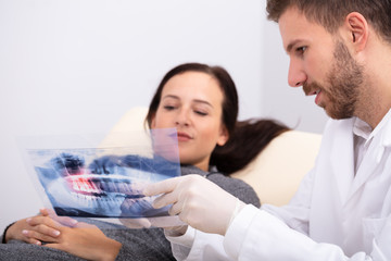 Male Doctor Explaining X-ray To Patient