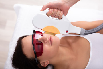Beautician Giving Laser Depilation Treatment To Woman Face