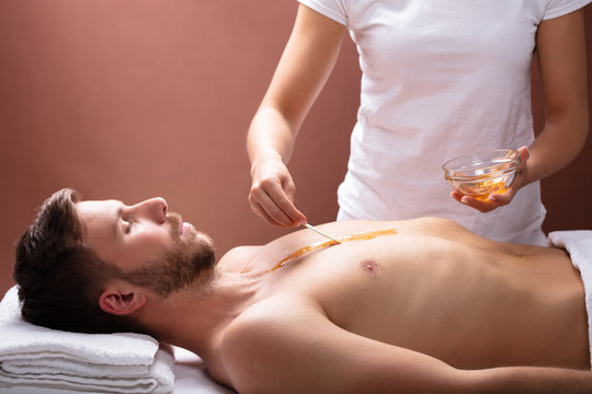 Therapist Applying Wax On Man's Chest