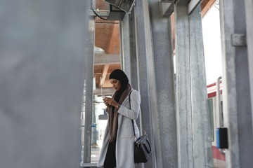 Woman using mobile phone in platform