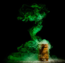 green smoke from wooden jar isolated at dark background