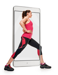 Side view of fit slim woman doing fitness exercises, concept virtual reality of the smartphone. going out of the device