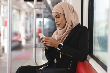 Young woman in hijab using cell phone in train