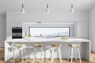 White kitchen with bar and ovens