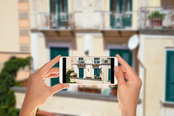 A tourist is taking a photo of typical Italian balcony in Amalfi, Italy on a mobile phone