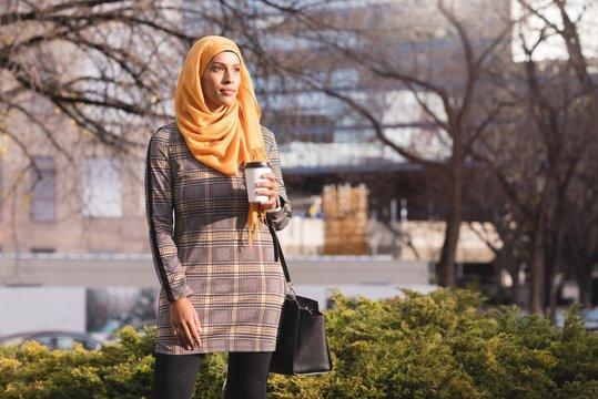 Woman having coffee in park