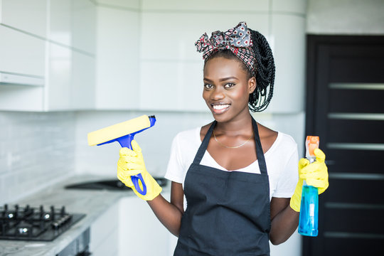 Portrait young african woman using spray to wipe windows glass