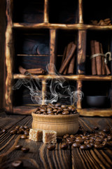 Hot steaming coffee beans in bowl on rustic wooden background