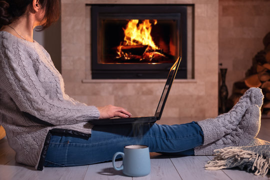 Young freelancer woman sits at the floor with a laptop on the fireplace background.