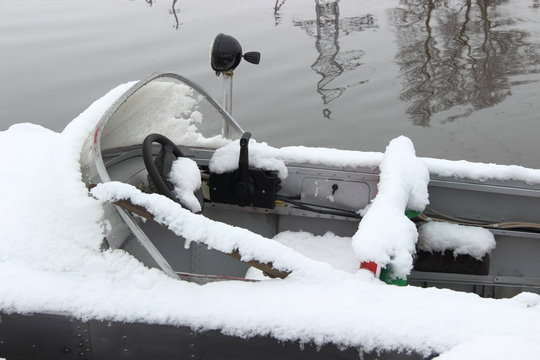 Cockpit of fishing motor boat in the snow - winter boating and storage of watercrafts on the water at the pier
