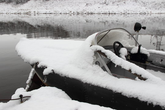 Bow part of fishing motor boat in the snow - winter navigation and outdoor storage of watercrafts on the water at the pier, side view