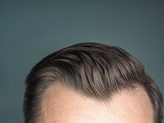 Pulled back hair style on unrecognizable male, towards gray