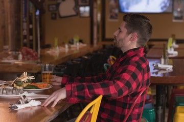 Man sitting at the table with drinks in pub