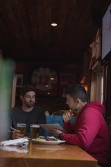 Friends discussing over digital tablet in pub