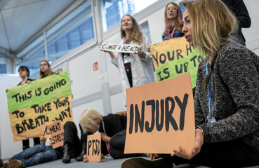 """Environmental activists hold placards during a """"Climate Is Health"""" protest during the COP24 U.N. Climate Change Conference 2018 in Katowice"""
