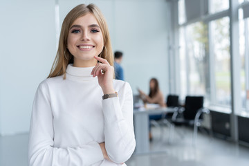 Beautiful young business lady is looking at camera and smiling while her colleagues are working in the background.