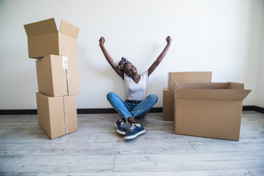 People, moving new place and repair concept - happy african american young woman with many cardboard boxes sitting on floor at home happy raised hands of relocation