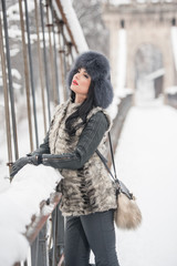 Attractive woman with black fur cap and gray waistcoat enjoying the winter. Side view of fashionable brunette girl posing against snow covered bridge. Beautiful young female with cold weather outfit