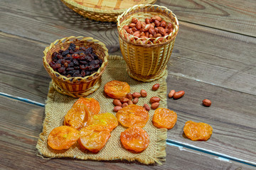 peeled raw peanuts dried apricots raisins on a wooden table background