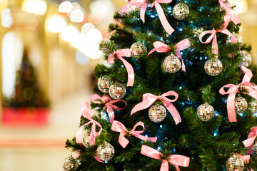 Picture of Christmas tree with balls with sequins, pink bows on blurred background
