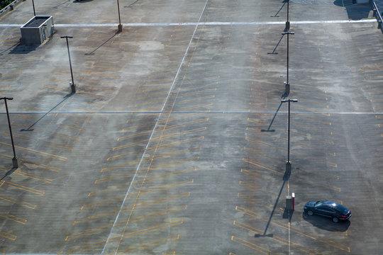 single car in large parking lot birds-eye view