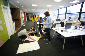 Startup business people in modern office. Group of young business people are working together with laptop. Freelancers sitting on the floor. tech startup, tech team.