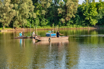 Novi Sad, Serbia - August 04, 2018: Danube island (Šodroš) near Novi Sad, Serbia. Fishermans sitting in boat and holding fishing rod.